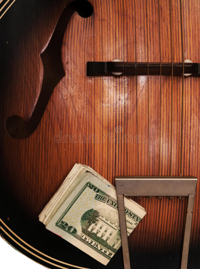 Vintage Acoustic Guitar And Money. Detail view of old, beat-up acoustic guitar, with a wad of U.S. paper money stuck in the tailpiece royalty free stock image