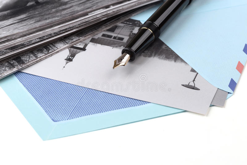 Vintage airmail envelope and fountain pen. Vintage airmail envelope with a photo and fountain pen over white royalty free stock photo
