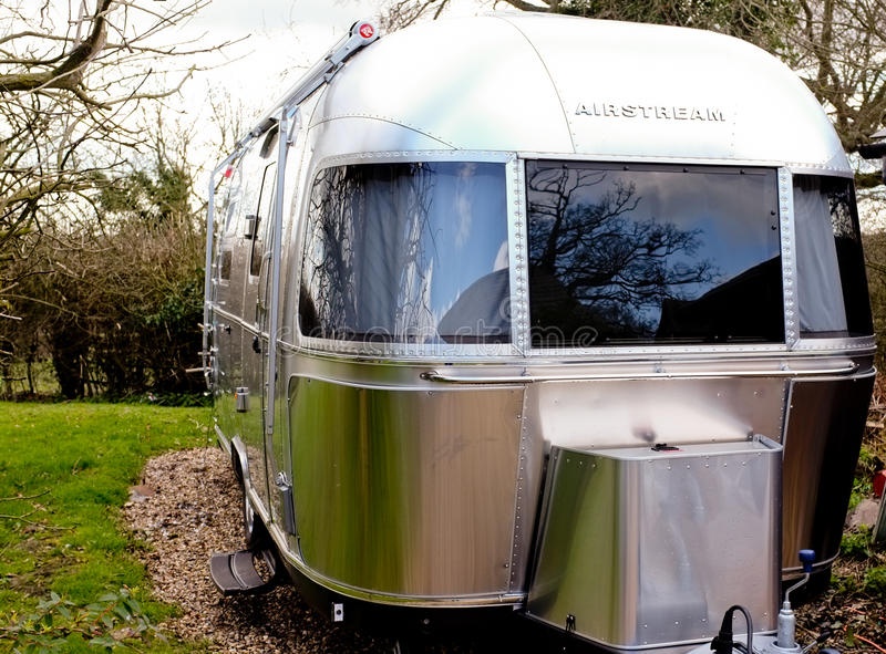 Vintage Airstream. Famous shape of a silver bullet Airstream trailer on a camp site. Useful for touring magazines and vintage articles royalty free stock images