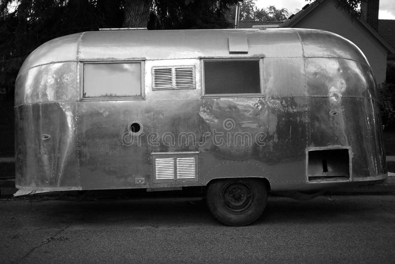 Vintage Airstream Trailer. Old vintage Airstream camper travel trailer black and white parked on the street stock images