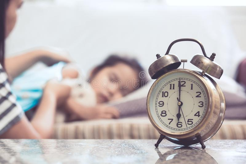 Vintage alarm clock on background of mother taking care child. Vintage alarm clock on background of mother taking care asian child girl while she sleeping in the royalty free stock photos