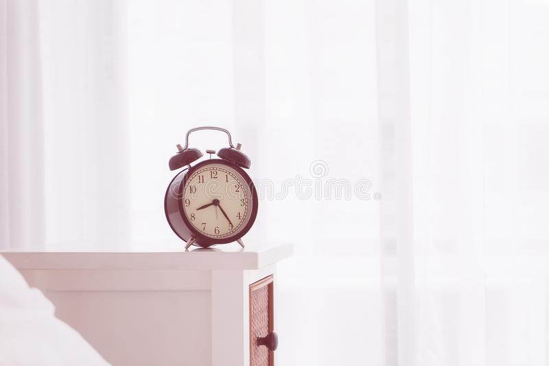 Vintage alarm clock on bedside table by windows. Vintage alarm clock on bedside table by morning windows royalty free stock photography