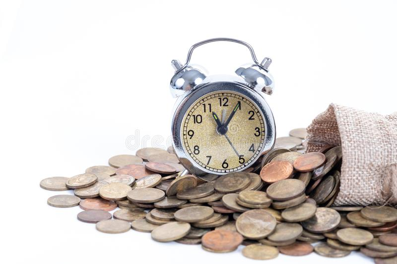 Vintage alarm clock bell with money bags and coins on white background.Time to invest, time value for money, family planning,. Money saving, finance saving and stock photo