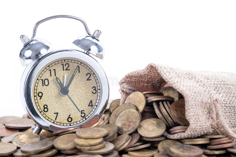 Vintage alarm clock bell with money bags and coins on white background.Time to invest, time value for money, family planning,. Money saving, finance saving and stock image