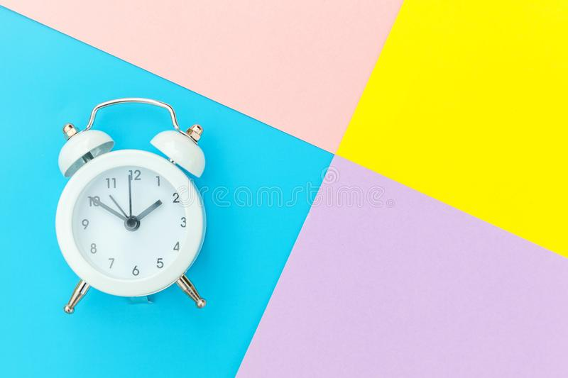 Vintage alarm clock isolated on blue yellow pink pastel colorful trendy geometric background. Ringing twin bell classic alarm clock isolated on blue yellow pink royalty free stock image