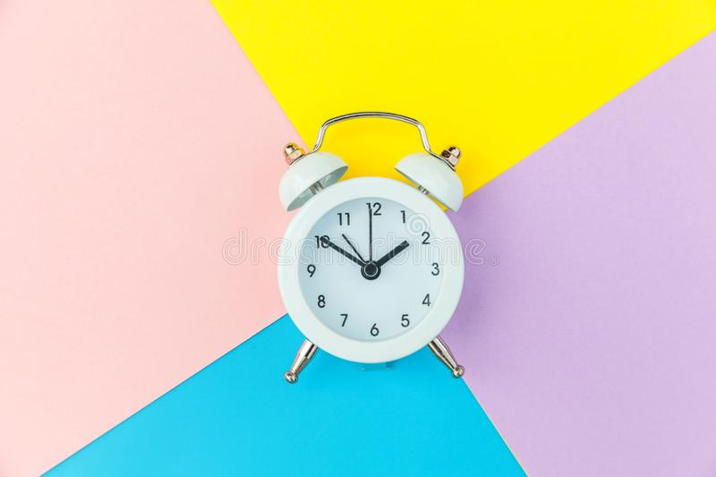 Vintage alarm clock isolated on blue yellow pink pastel colorful trendy geometric background. Ringing twin bell classic alarm clock isolated on blue yellow pink stock photo