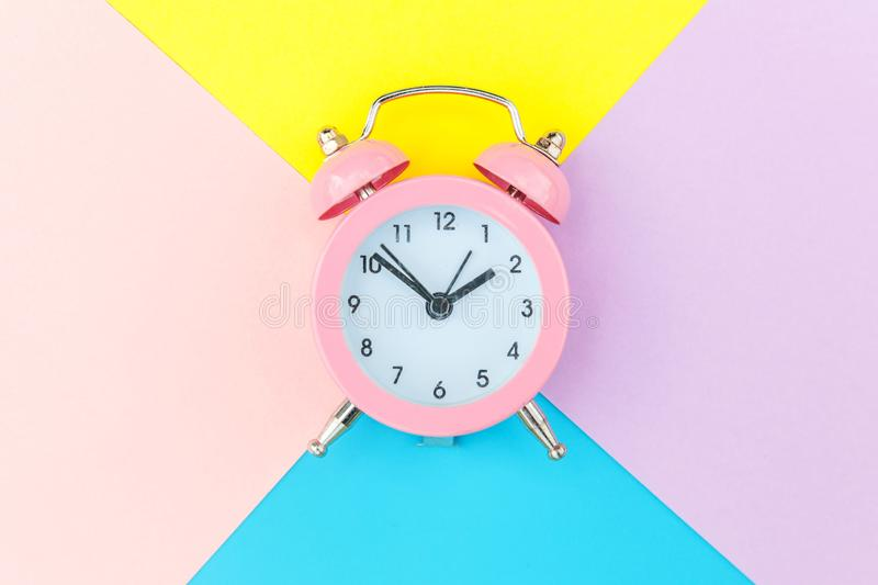 Vintage alarm clock isolated on blue yellow pink pastel colorful trendy geometric background. Ringing twin bell classic alarm clock isolated on blue yellow pink royalty free stock photo