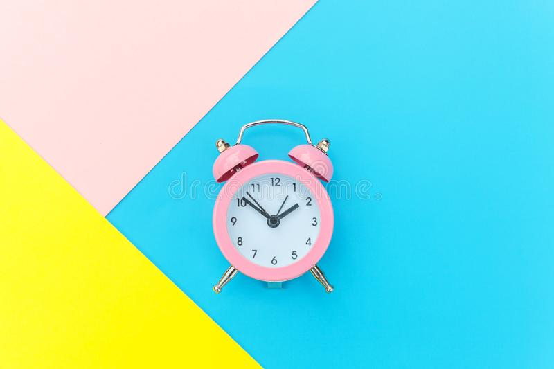 Vintage alarm clock isolated on blue yellow pink pastel colorful trendy geometric background. Ringing twin bell classic alarm clock isolated on blue yellow pink royalty free stock images