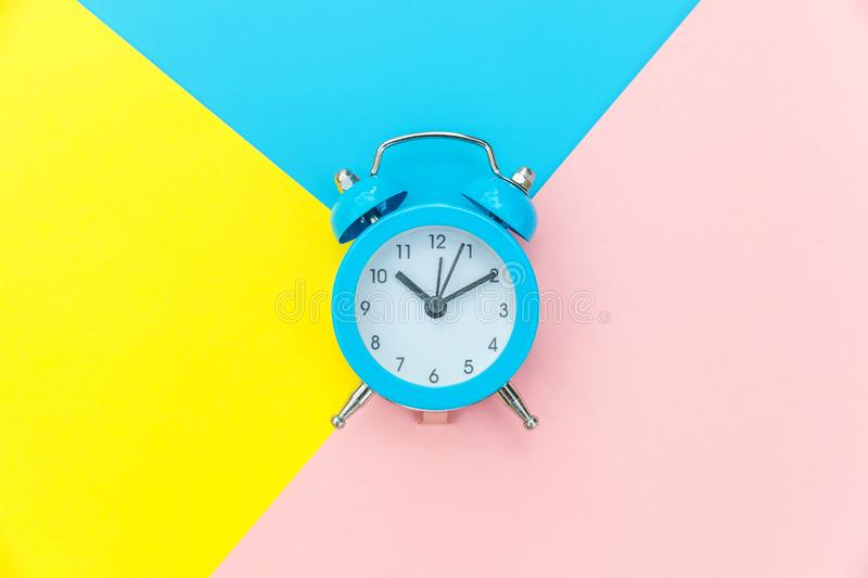 Vintage alarm clock isolated on blue yellow pink pastel colorful trendy geometric background. Ringing twin bell classic alarm clock isolated on blue yellow pink stock image