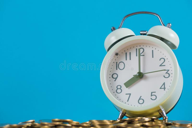 Vintage alarm clock on the pile of gold coin with blue background, time and business finance concept stock photography