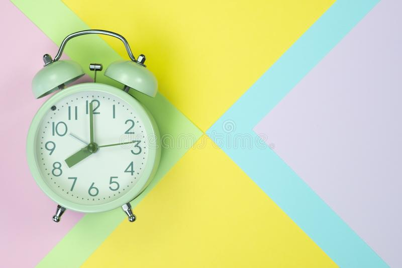 Vintage alarm clock on sweet pastel colored paper top view, back stock photography