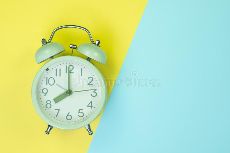 Vintage alarm clock on sweet pastel colored paper top view, back royalty free stock photography