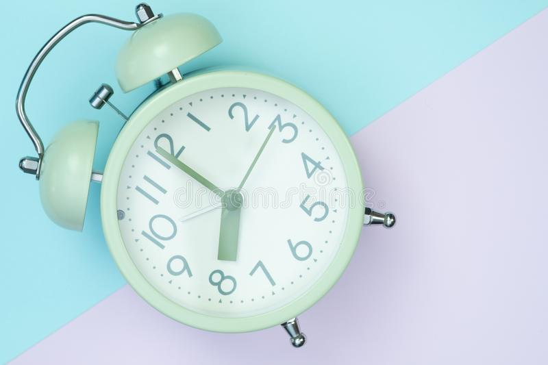 Vintage alarm clock on sweet pastel colored paper top view, back royalty free stock image
