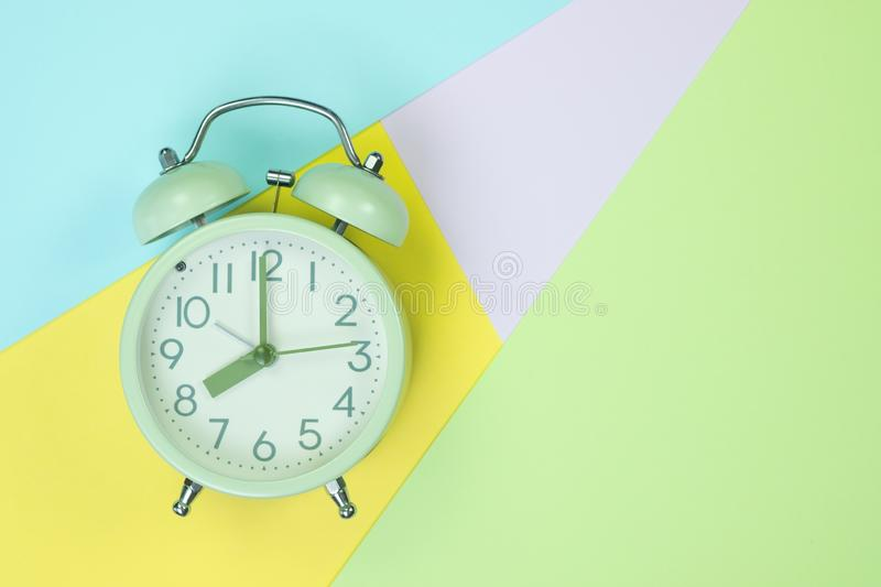 Vintage alarm clock on sweet pastel colored paper top view, background texture, pink, purple, yellow, beige, green and blue colour royalty free stock images