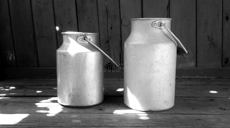 Vintage aluminum milk cans on wooden floor royalty free stock photography