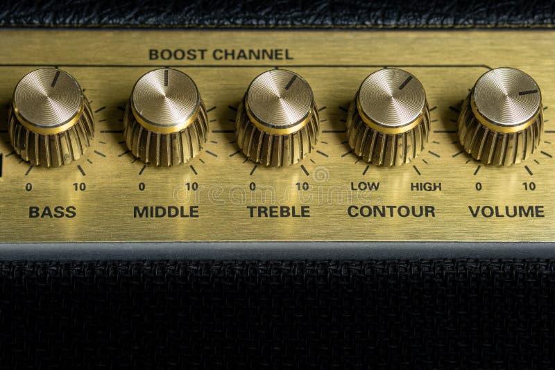 Vintage amplifier five knobs horizontal closeup, music recording studio equipment, bottom copy space. Vintage amplifier five knobs horizontal closeup, music royalty free stock photo