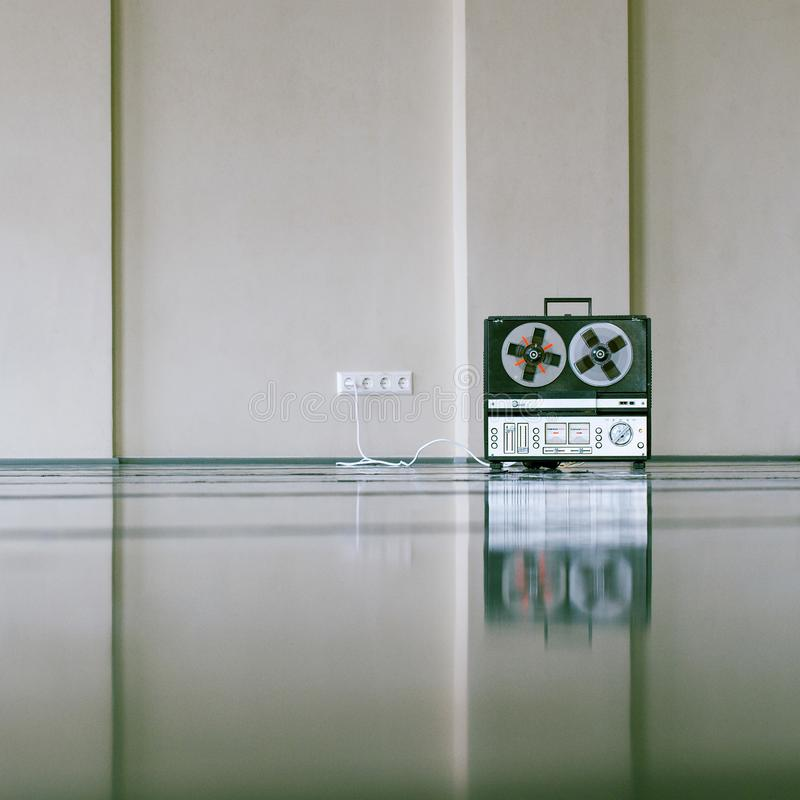 Vintage analog magnet tape recorder standing on the floor near wall royalty free stock images