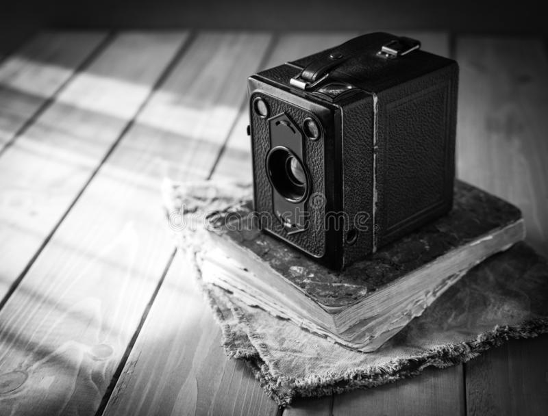Vintage analogue film camera on a wooden table, old book, clothl. Black and white photo. Copy space stock image