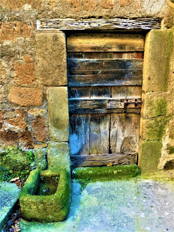 Vintage ancient door, time and history, wood, stones and moss. Enchanting entrance and fairytale, locked and secret escape from reality, beam and wall, art stock photo