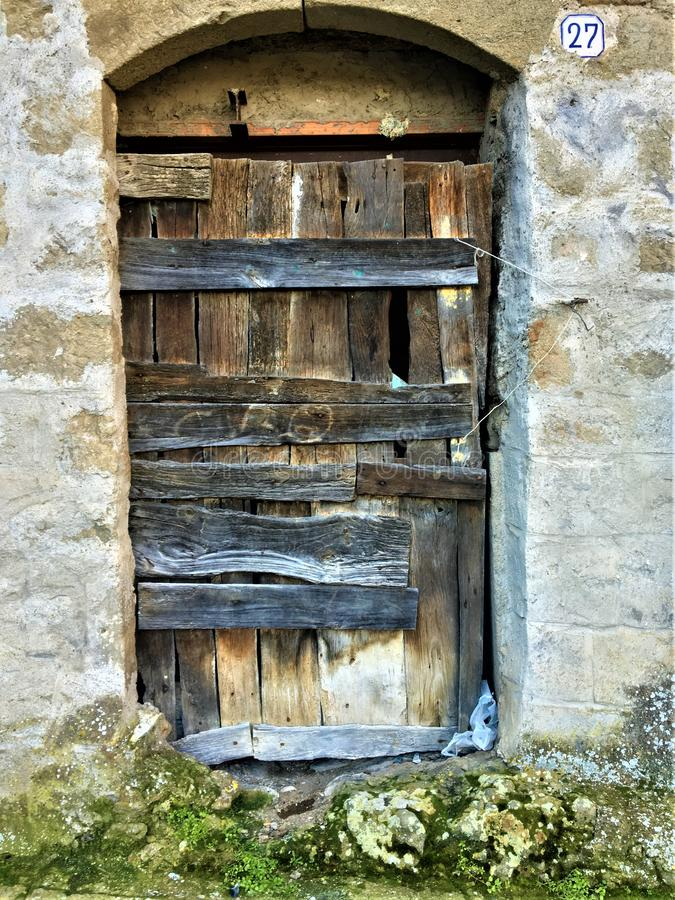 Vintage ancient door, time and history, wood, stones and moss. Enchanting entrance and fairytale, locked and secret escape from reality, beam and wall, art stock photography