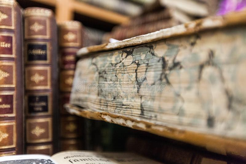 Vintage, antiquarian books pile on wooden surface. Ancient education literature literacy wisdom erudition knowledge royalty free stock image