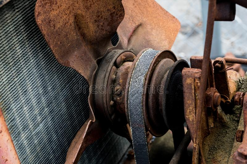 Vintage antique automotive tractor rusty fan blade and belt behind the radiator stock photos