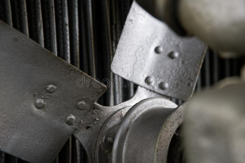 Vintage antique automotive tractor rusty fan blade and belt behind the radiator with pulleys showing. royalty free stock images