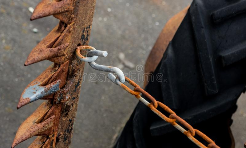 Vintage antique automotive tractor wheel and cutter implement and chain showing rust stock photo