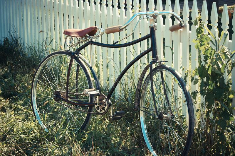 Antique bicycle leaning on a fence stock photos