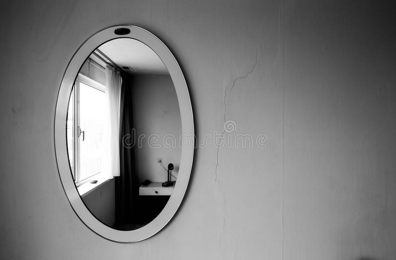 Vintage antique mirror on white old wall black and white. Vintage antique mirror on white old wall dark shadows royalty free stock photography