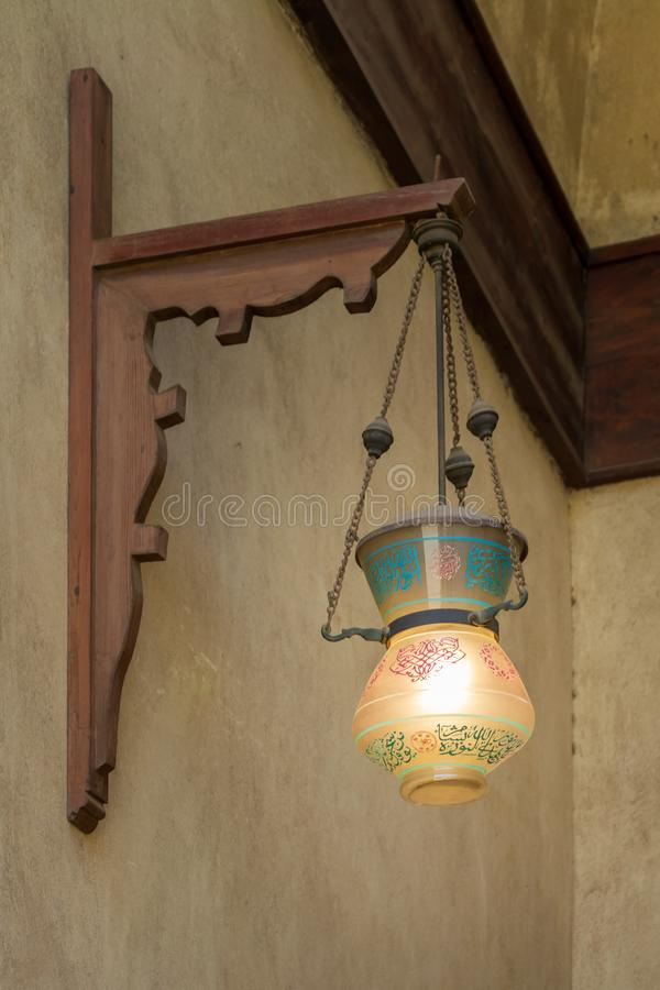 Vintage Arabic glass street lantern hanged on a wooden pole. Dome of Sultan Al Nassir Qalawun, Cairo, Egypt stock photos