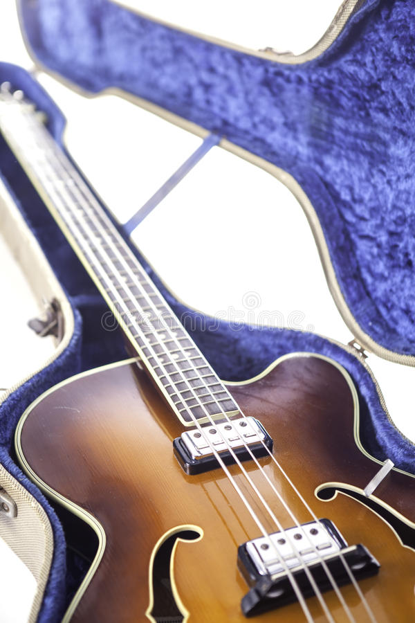 Vintage archtop bass guitar. Vintage archtop semi-acoustic bass guitar in tweed case royalty free stock photo