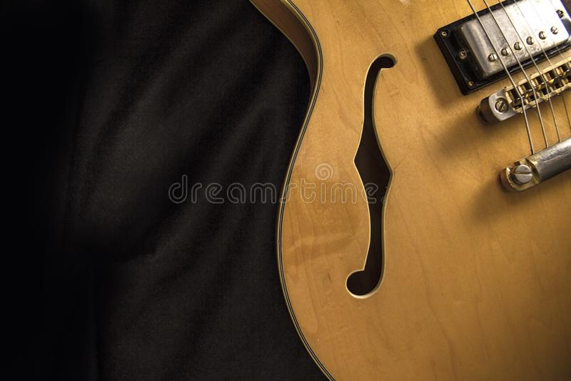 Vintage archtop guitar in natural maple close-up from above on black background, F-hole detail. Vintage archtop guitar in natural maple close-up from above on royalty free stock photography