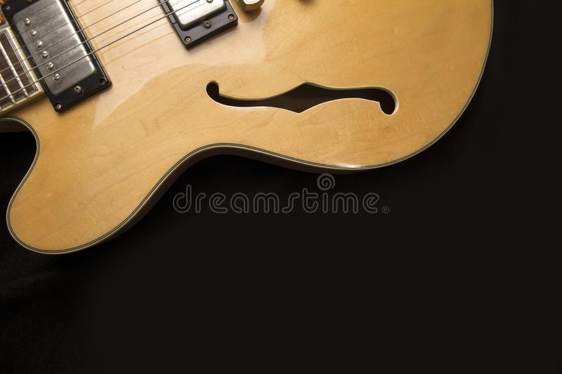 Vintage archtop guitar in natural maple close-up from above on black background, F-hole detail. Vintage archtop guitar in natural maple close-up from above on stock image
