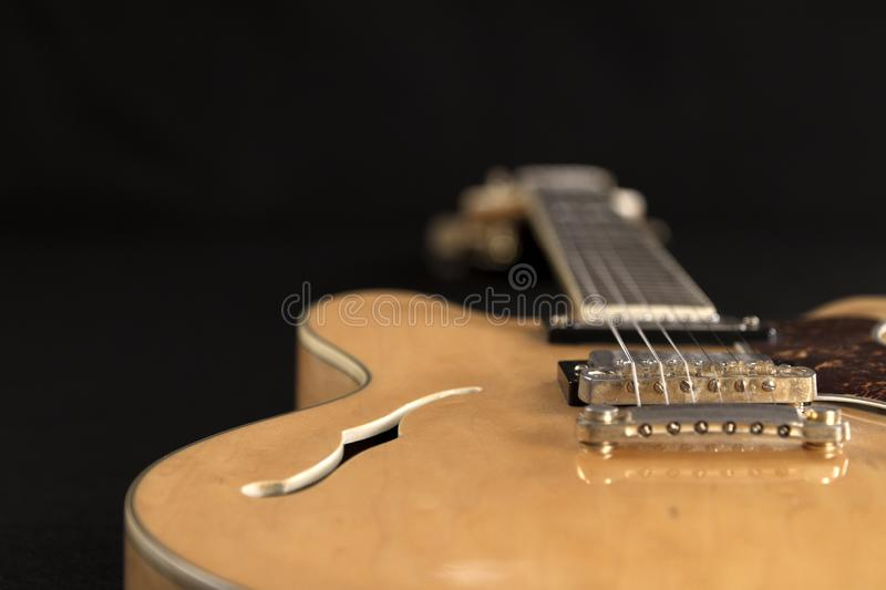 Vintage archtop guitar in natural maple close-up high angle view on black background, bridge and F-hole detail in selective focus. Vintage archtop guitar in stock image