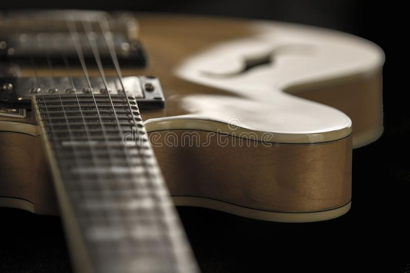 Vintage archtop guitar in natural maple close-up high angle view on black background, frets and veins of maple wood detail in. Vintage archtop guitar in natural royalty free stock photos