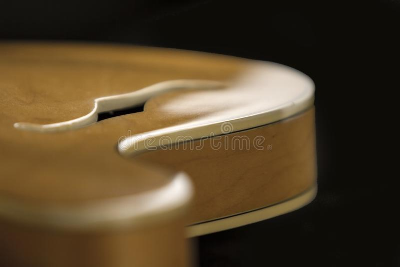 Vintage archtop guitar in natural maple close-up high angle view with F-hole detail in selective focus and black background. Vintage archtop guitar in natural stock photo