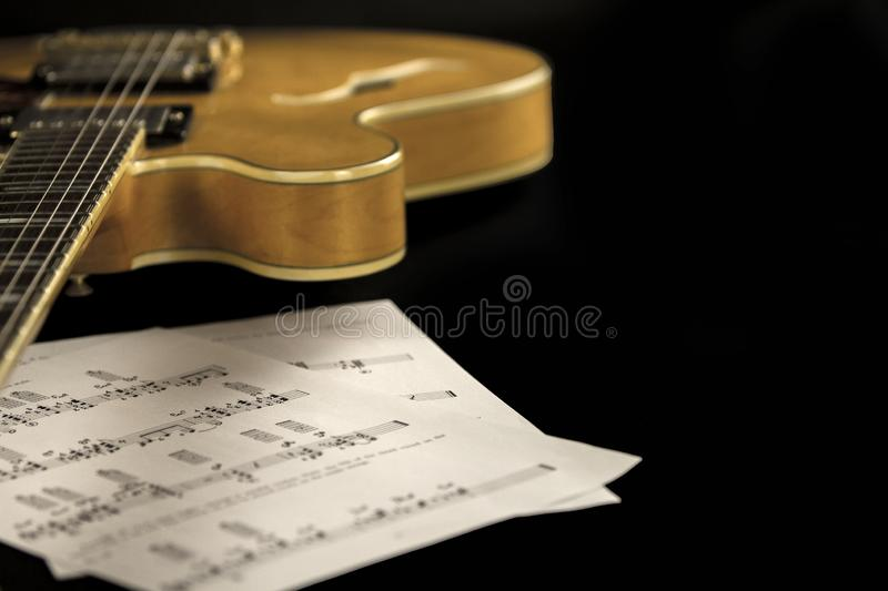 Vintage archtop guitar in natural maple close-up high angle view with music sheets on black background royalty free stock photos