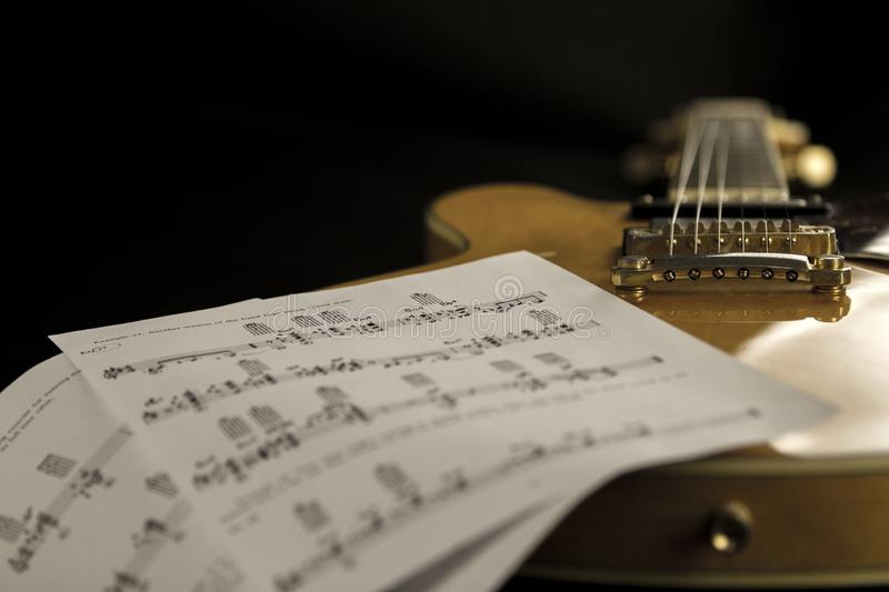Vintage archtop guitar in natural maple close-up high angle view with music sheets on black background stock photo