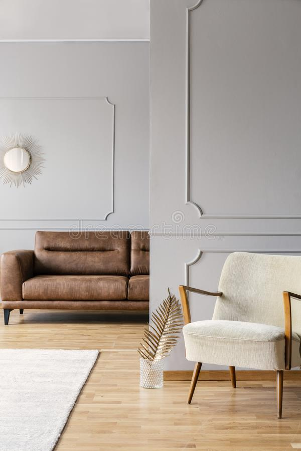 Vintage armchair in minimal living room of elegant apartment with leather sofa. Vintage armchair in minimal living room of elegant apartment with brown leather royalty free stock image