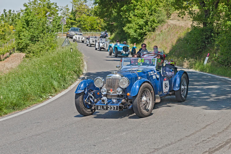 Vintage Aston Martin Le Mans in Mille Miglia 2014. The crew Moceri - Cavalleri on an old racing car Aston Martin Le Mans (1933) leads a line of classic cars in stock image