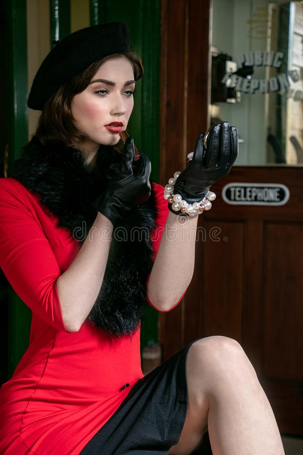 Vintage attractive female wearing red dress and black beret, sitting on suitcases applying her makeup at train station stock image
