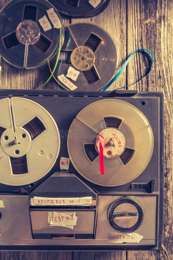 Vintage audio reel recorder with roll of tape and microphone. On old table stock photography