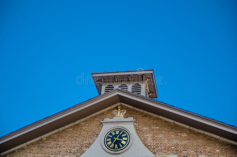 Vintage back face clock with gold Roman numerals on an old brick building with blue sky background. stock images