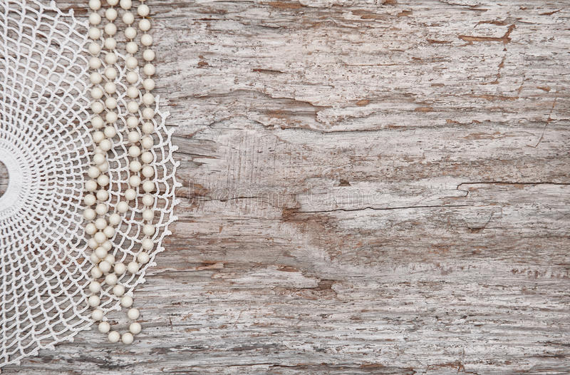 Vintage background with bead necklace and lace on the old wood stock photography