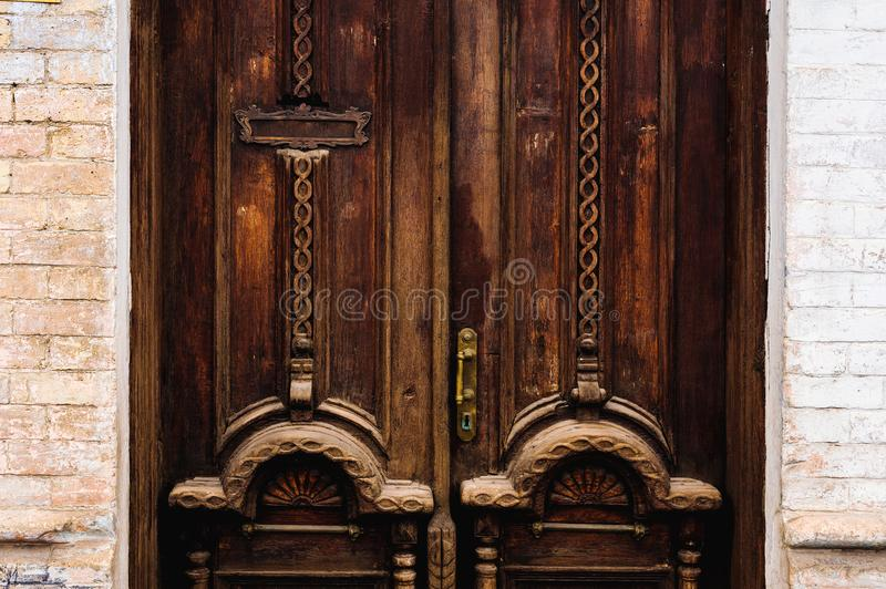 Vintage background. Brass-made old handle with Elements of an carved wooden door decorated with massive wooden. Simulating weaving. An old concept of old stock photos