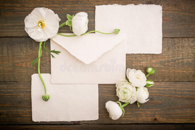 Vintage background made of paper post cards, envelope and white flowers on wood background. Flat lay, top view. Vintage background made of paper post cards royalty free stock photo