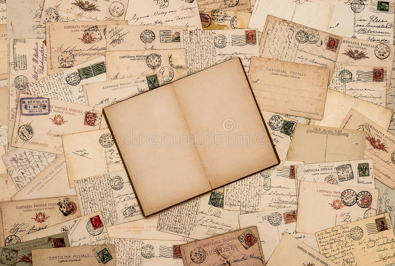 Vintage background with old handwritten post cards. Nostalgic vintage background with old handwritten post cards and open empty book page royalty free stock photos