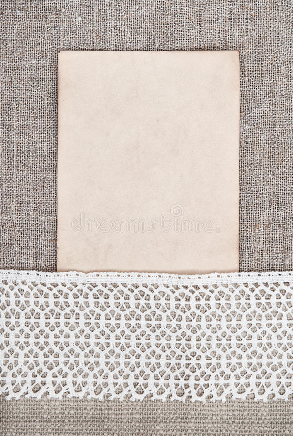 Vintage background with old paper on lace fabric and burlap royalty free stock image