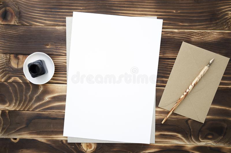A vintage background with A4 paper list, a nib pen and an ink well, top view with a place for text royalty free stock image